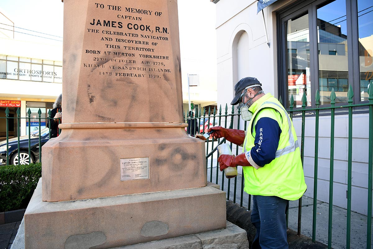 A worker paints over graffiti on a Captain Cook statue