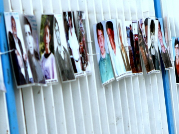 The cover of the report shows pictures of missing persons at the UN building in Pristina.