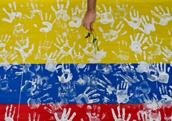 A man places a flower on a Colombian flag