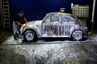 Une coccinelle Volkswagen (Fusca) de 1978 est en train d'être lavée dans une station-service de Rio de Janeiro, au Brésil. © Yasuyoshi Chiba / AFP