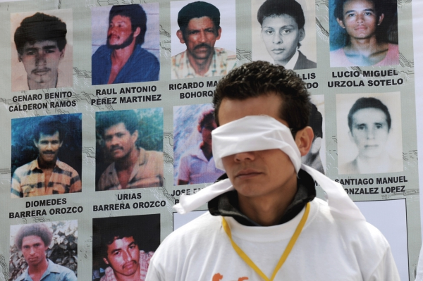 A relative of a person disappeared by the Colombian AUC paramilitary guerrillas, wearing a blindfold, demonstrates against the government during a protest on July 8, 2008, in Bogota. The protesters want better treatment from the government and to be given information about where the bodies of their loved ones are.