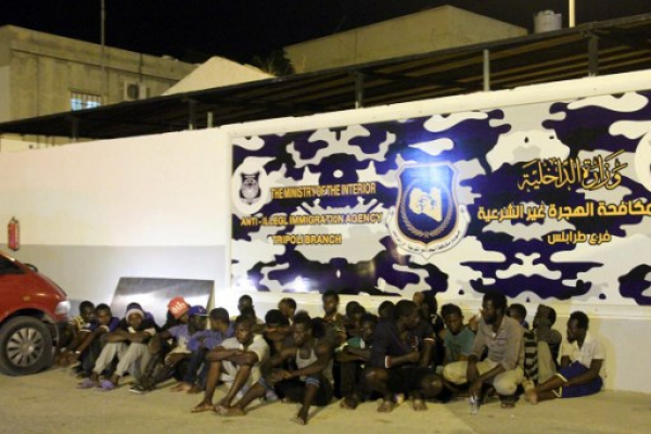 Men from African countries sit outside Tripoli's anti-illegal immigration agency on June 4, 2017. Seven migrants from sub-Saharan Africa were found dead in an abandoned refrigerator truck near the Libyan capital, according to a senior official in the fight against illegal immigration.