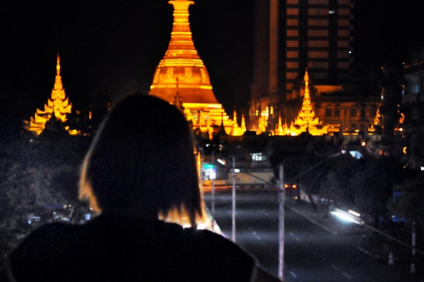 A woman looks down at Sule Pagoda during evening in Yangon