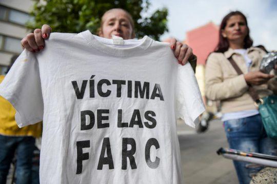 """Una mujer sostiene una camiseta en la que se lee """"Víctima de las FARC"""""""