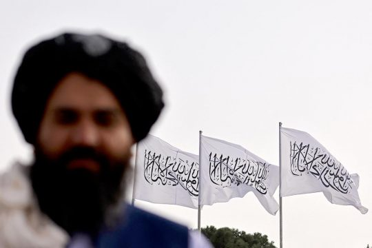 Taliban fighter posing in front of Taliban flags