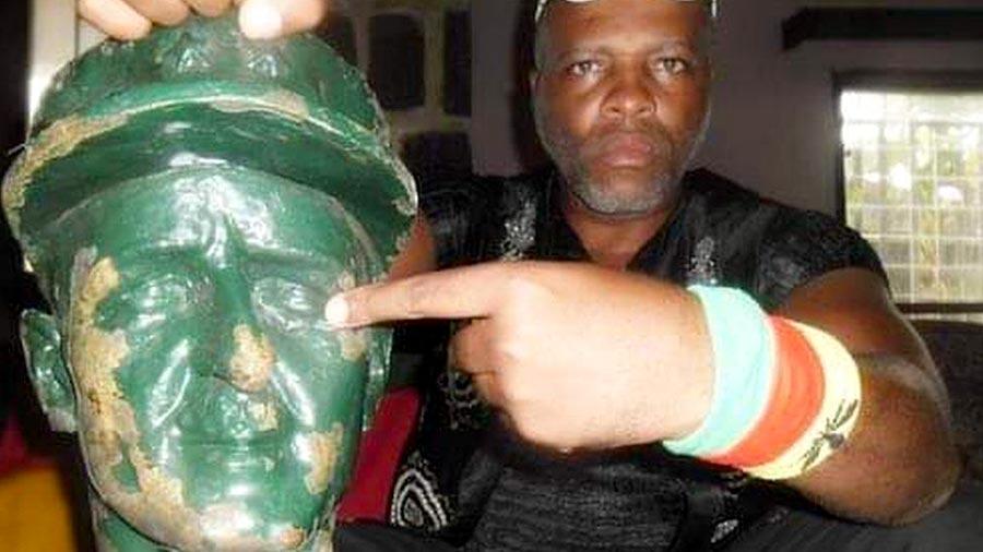 André Blaise Essama tient fièrement dans sans main la tête d'une statue de bronze, qu'il montre du doigt.