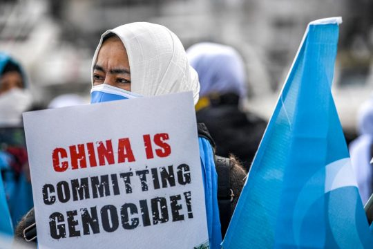 "A veiled protester holds a sign that reads ""China is committing genocide!"""