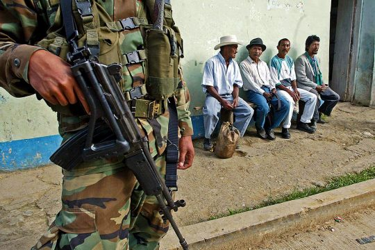 A Colombian soldier stands near civilians in the street