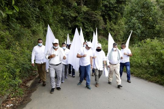 Former FARC members walk down a road dressed in white and carrying white flags.