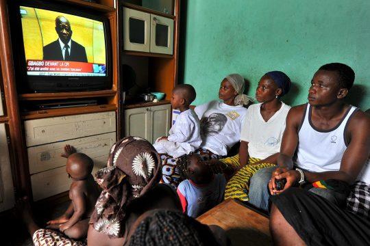 Une famille ivoirienne regarde une retransmission télévisée de Laurent Gbagbo devant la Cour pénale internationale (CPI).