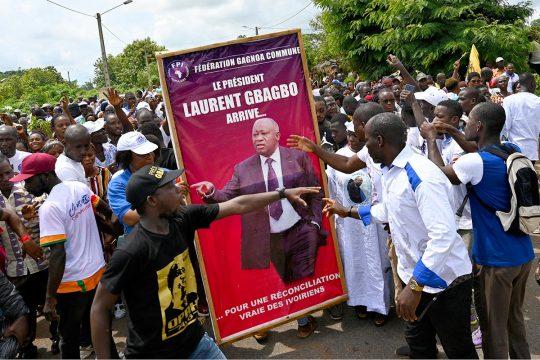 """Des ivoiriens sont rassemblés autour d'une affiche avec une photo de Laurent Gbagbo : """"Le président Laurent Gbagbo arrive... pour une réconciliation vraie des Ivoiriens"""""""
