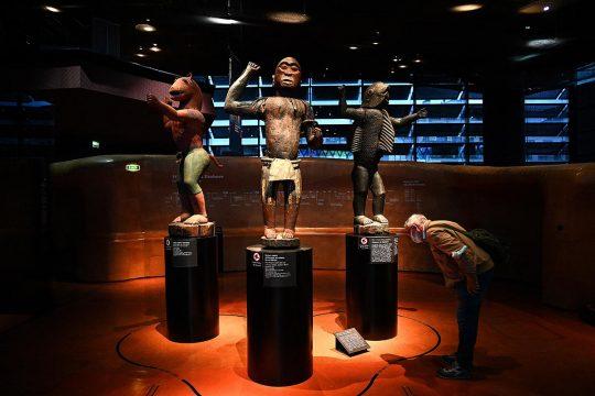 Un visiteur du musée du quai Branly observe 3 statues issues des trésors royaux d'Abomey.