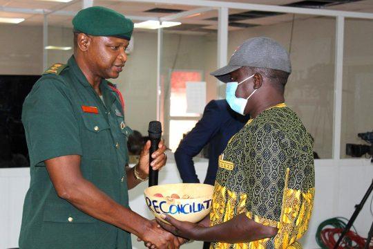 Scène de réconciliation à la TRRC gambienne entre un militaire et un civil