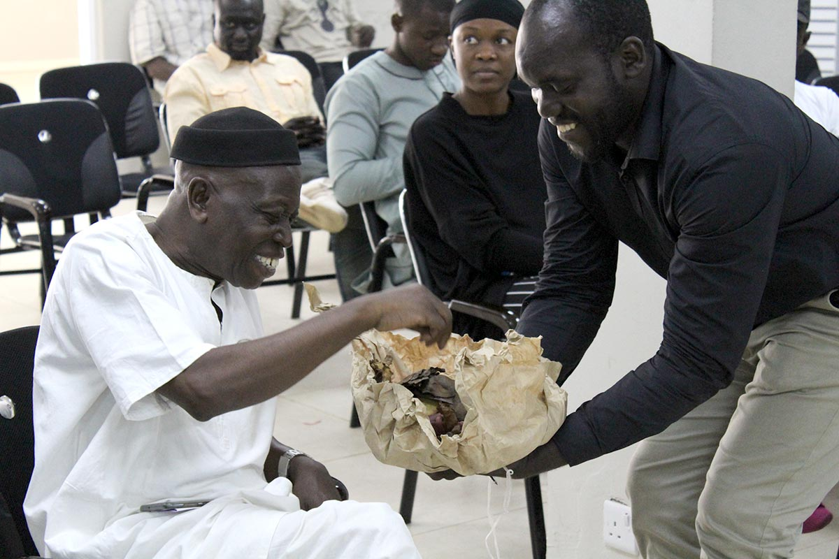 2 gambians share cola nuts as a sign of reconciliation