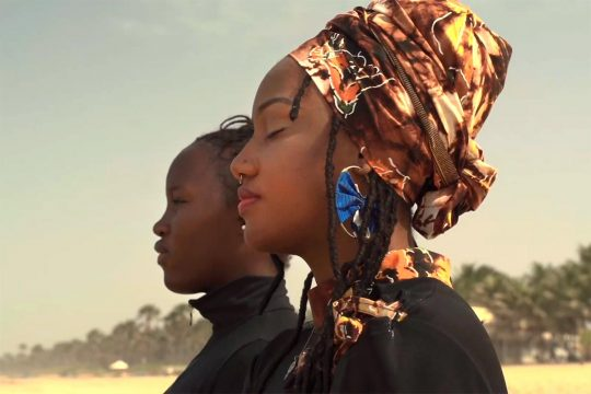 Toufah Jallow an another women watch the horizon from a Gambian beach