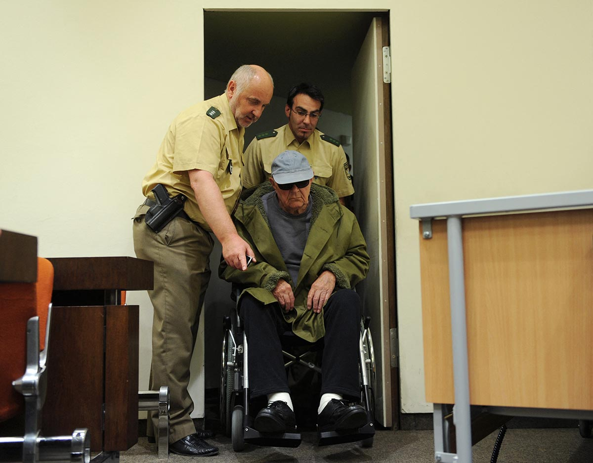 Defendant John Demjanjuk arrives in a wheelchair at court for his trial in Germany, assisted by two police officers.