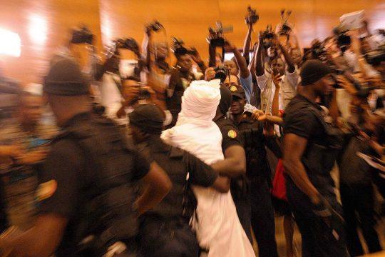Hissène Habré entre les mains des policiers (et entouré de journalistes) lors de son procès au Sénégal en 2015