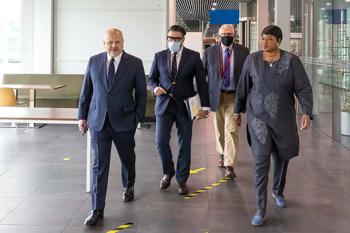 Fatou Bensouda and Karim Khan walk side by side in the corridors of the International Criminal Court