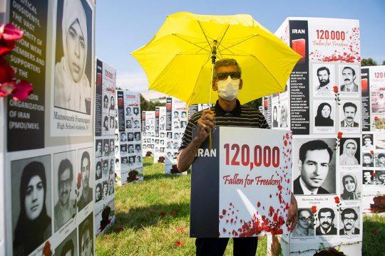 Militant devant des milliers de photos de victimes des massacres de 1988 en Iran