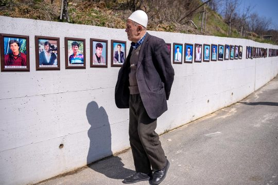 An old man looks at photos of war victims on a wall in Kosovo.