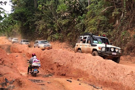 A Finnish court crosses Liberia in a 4x4 convoy along muddy tracks.