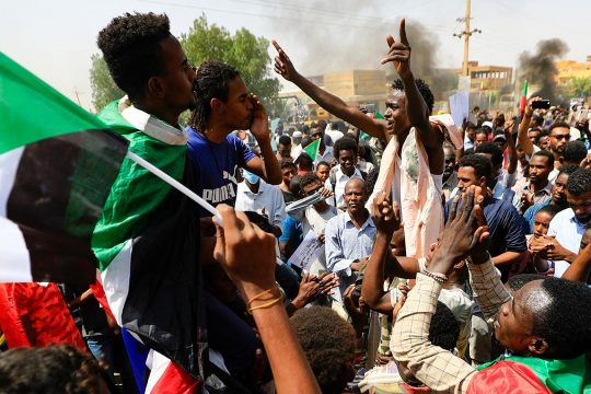 Des manifestants soudanais défilent à Khartoum, brandissant des drapeaux du Soudan