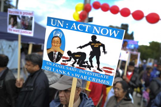"During a demonstration, a sign displays this text message: ""UN: act now"""