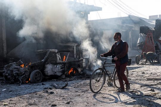 Syrian civilian riding his bike through the street near the remains of a car bomb explosion