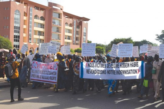 """Demonstrators march in the street carrying a banner """"We, the victims of the Hissein Habré regime, demand our compensation""""."""