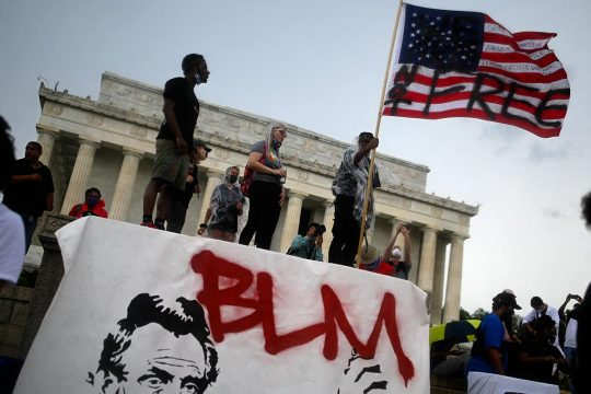 "A man holds an American flag with the words ""Not free"" on it, in front of the Lincoln Memorial in Washington (USA)"