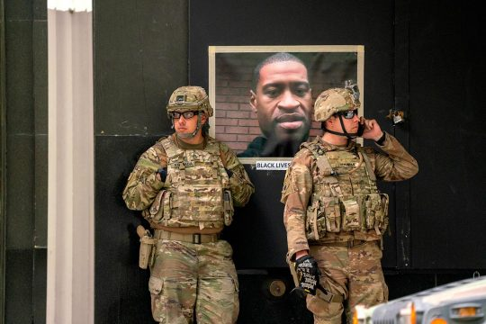 Two American soldiers in front of a portrait of George Floyd posted in the street